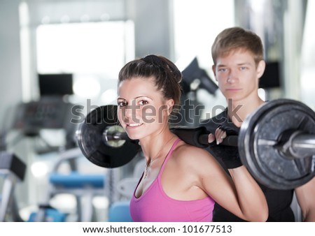 woman with coach  doind exercises with bar