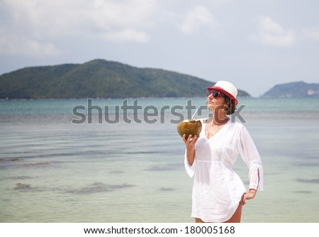 Woman with coconut on the beach - stock photo
