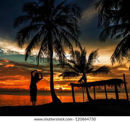 Woman with coconut palm in silluate background - stock photo