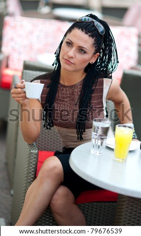 woman with coffee in outside bar terrace - stock photo