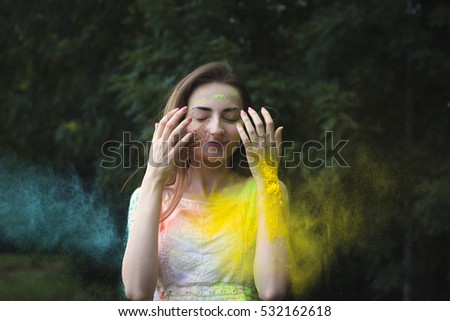 Woman with color powder on a Holi festival covering her face