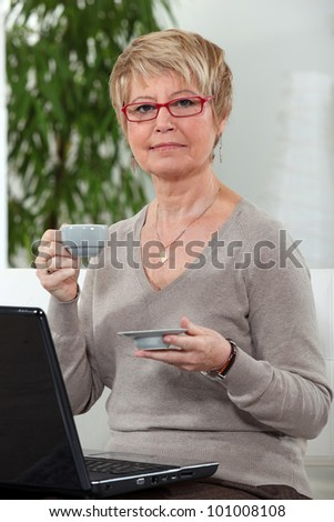 Woman with computer and coffee cup - stock photo