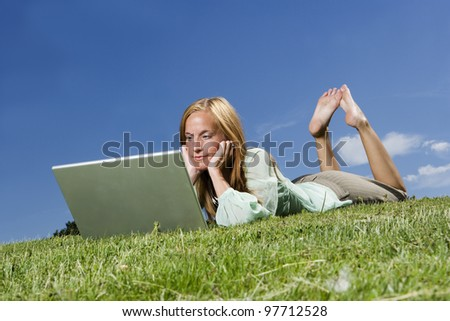 Woman with computer in the grass towards blue sky - stock photo