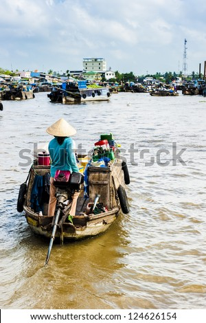 woman with conical hat driving her machine boat to floating market on Mekong river - stock photo