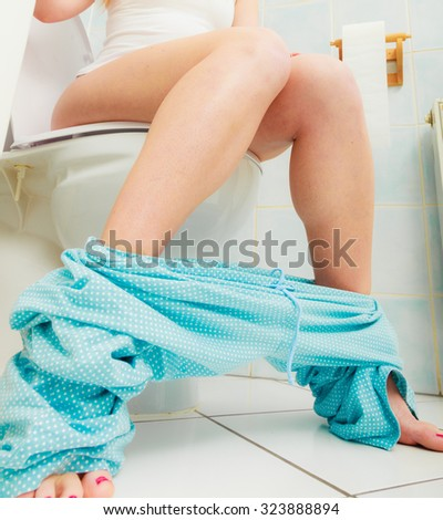 Woman with constipation or diarrhoea sitting on toilet with her blue pajamas down around her legs - stock photo