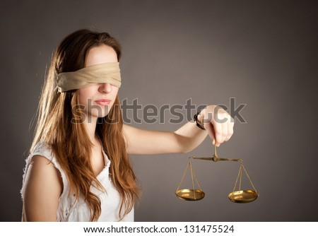 woman with covered eyes holding a justice scale - stock photo