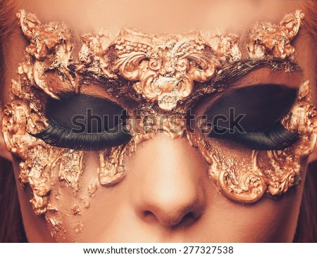 Woman with creative carnival mask on her face  - stock photo