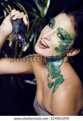 woman with creative make up like snake and rat in her hands, halloween horror closeup - stock photo