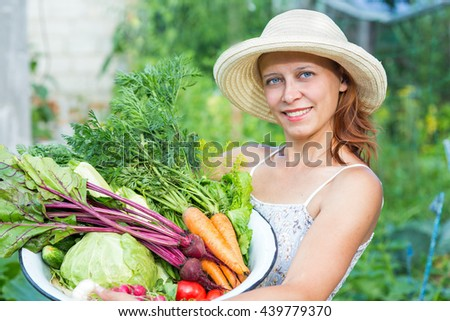 Woman with crop of fresh vegetables in the garden