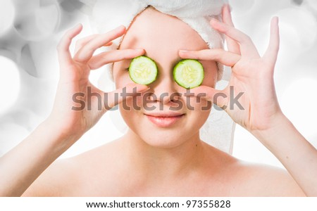 Woman with cucumbers on eyes with lights in the background - stock photo