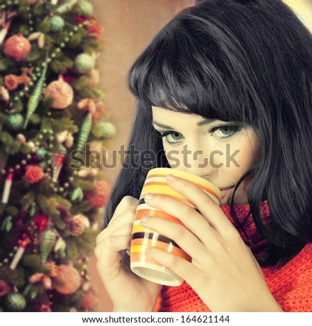 woman with cup against  christmas tree