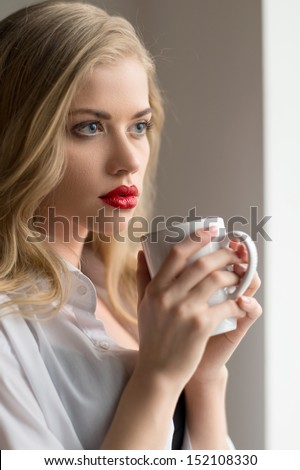 Woman with cup of coffee. Beautiful blond hair woman holding a cup and looking away - stock photo