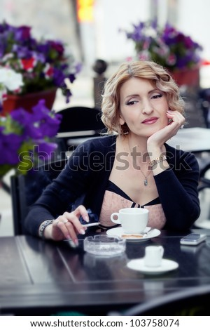 Woman with cup of coffee in summer cafe - stock photo