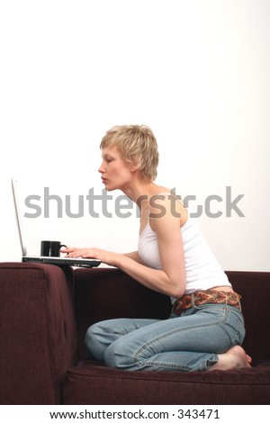 woman with cup of coffee sitting on sofa is reading message on her laptop
