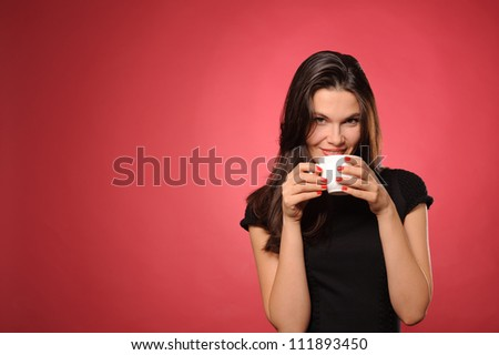 Woman with cup of coffee, tea or hot chocolate, against the red background - stock photo