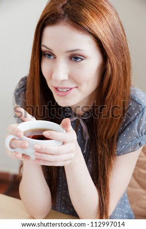 Woman with cup of tea at the cafe - stock photo