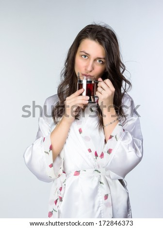 Woman with cup of tea  in peignoir early morning. On grey background.