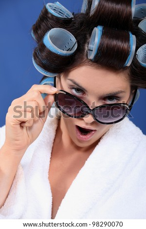 woman with curler wearing bath robe and sunglasses
