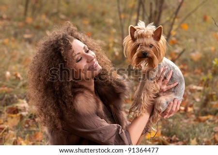 woman with curls and a little dog in nature, fall - stock photo