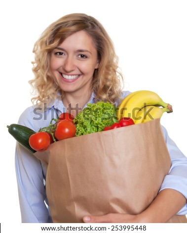 Woman with curly blond hair and a bag full of healthy food