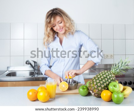 Woman with curly blond hair preparing orang juice in the kitchen - stock photo