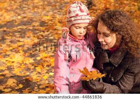 Woman with daughter and collect maple leaves in autumnal park