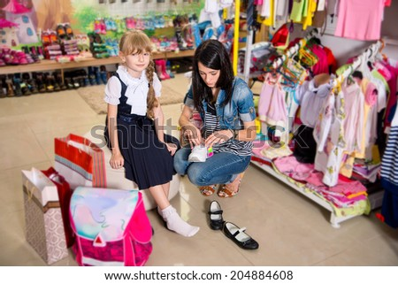 woman with daughter buying shoes - stock photo