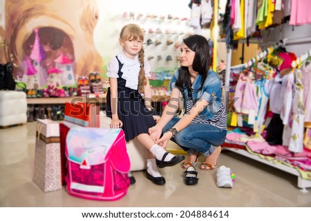 woman with daughter buying shoes