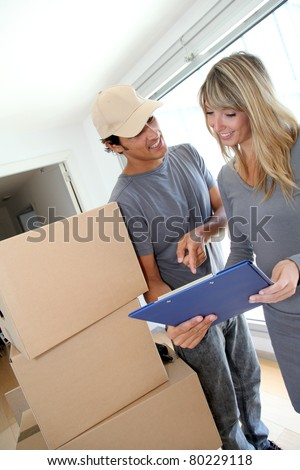 Woman with delivery man checking order contract - stock photo