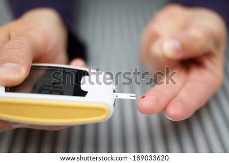 Woman with diabetes doing a blood test with a glucometer - stock photo