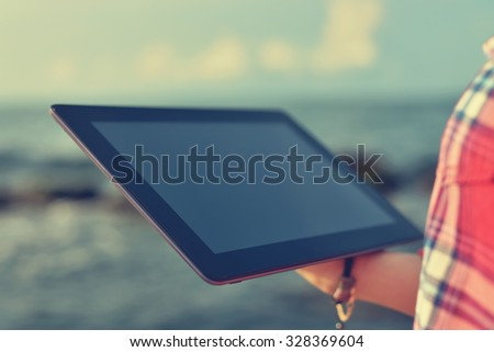 Woman with digital tablet at beach. Vintage photo - stock photo