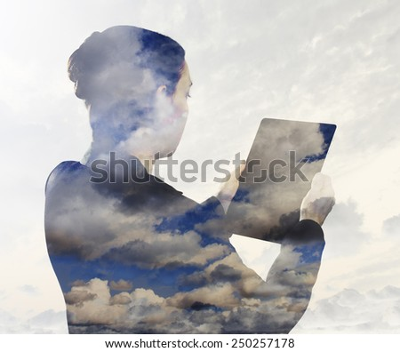 Woman with digital tablet composited with images of clouds  - stock photo
