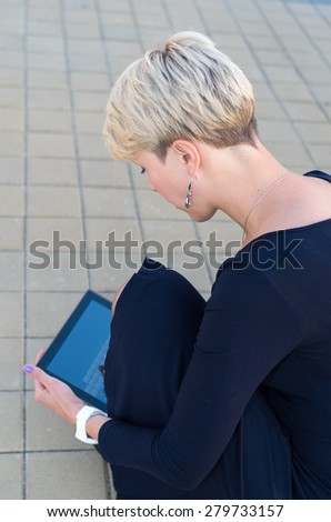 Woman with digital tablet in the city. European woman using tablet pc computer outdoor on a city street. Business woman with tablet pc in office district. Sad businesswoman. Student woman.