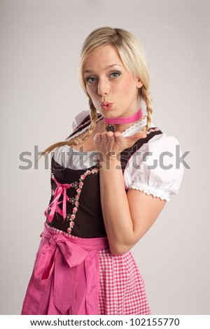 woman with dirndl makes a kiss-mouth/young blond woman with dirndl dress makes a kiss-mouth/blond woman with dirndl - stock photo