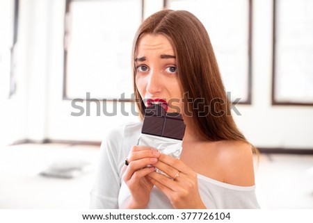 Woman with disappointed emotions thinking about sweet food worrying about calories and weight sitting in the sport gym - stock photo