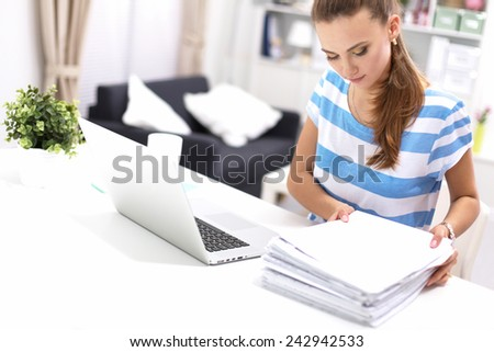 Woman with documents sitting on the desk and laptop