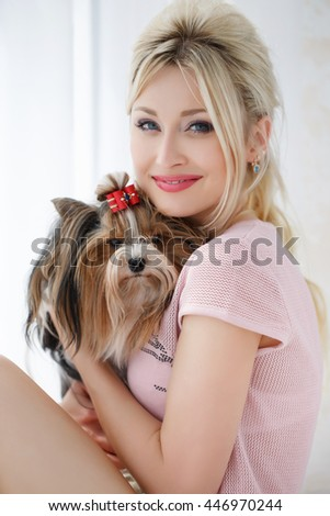 Woman with dog. Beautiful young woman training her small Maltese dog at home. Portrait of smiling girl - stock photo