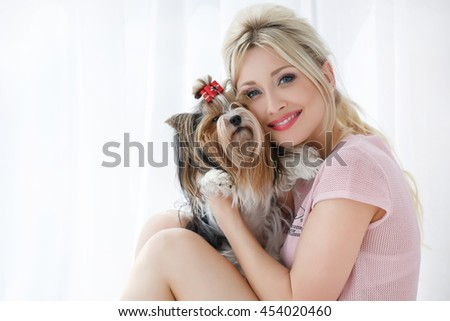 Woman with dog. Beautiful young woman training her small Maltese dog at home. Portrait of smiling girl. home - stock photo