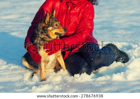 Woman with dog in snowy field - stock photo