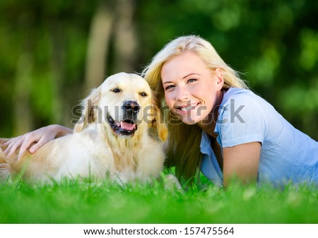Woman with dog lying on the green grass in the park - stock photo
