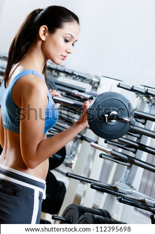 Woman with dumbbells in sport centre - stock photo