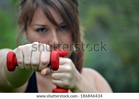 Woman with dumbbells in the park - stock photo