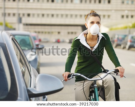 woman with dust mask commuting on bicycle - stock photo