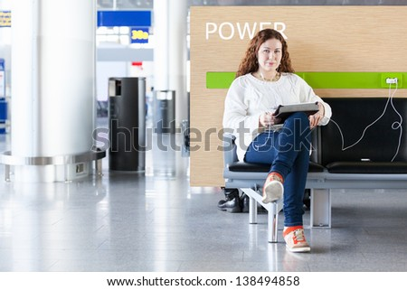 Woman with electronic devices near place to charge your phone. Copyspace - stock photo
