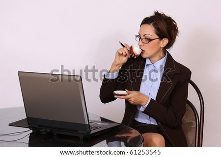Woman with eyeglasses working on lap top computer and drinking coffee