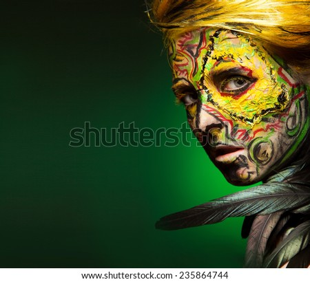 woman with face-art and body art paint. Yellow hair and red painted hand. Like bird. Feather decorated