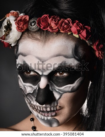 Woman with face-art. Skull on the face.