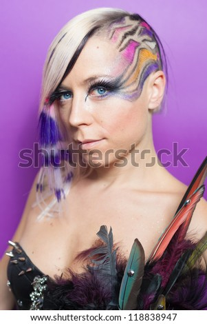 Woman with feathers,  multicoloured hair and blue eyes on purple background
