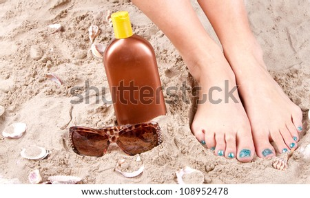 Woman with feet in the sand with sunglasses and sunscreen. - stock photo