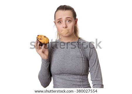 woman with first aid plaster over mouth unable to eat a muffin